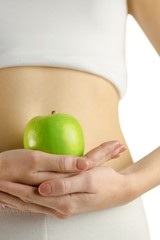 Slim woman holding green apple