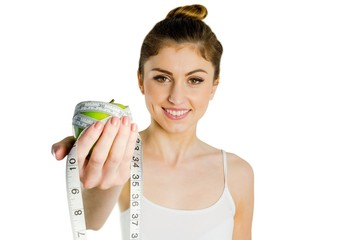 Slim woman holding apple and measuring tape