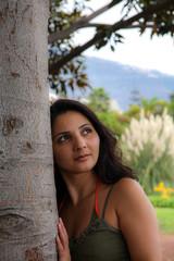 Frau an Baum blickt nach oben