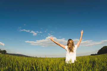 Young woman enjoying nature and sunlight in wheat field