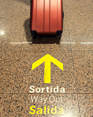 The suitcase is next to the exit signs in English, Spanish and C