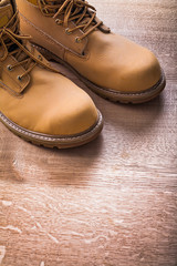 close up view two working boots On Wooden Board