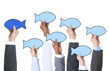 Business People Holding Fish Symbol Contrasts Concept