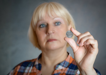 Woman holding coin on grey background. Selective focus.