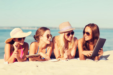 group of smiling young women with tablets on beach