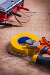 nippers screwdriver insulating tape multimeter On Wooden Board