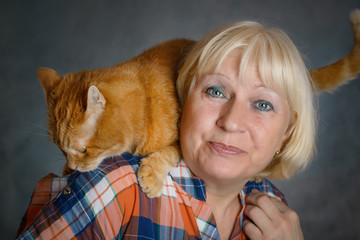 Beautiful aged woman hugging her red cat on grey background.
