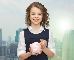 happy girl holding piggy bank and coin