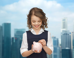 happy girl putting coin into piggy bank