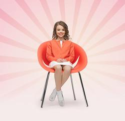 happy little girl sitting on designer chair