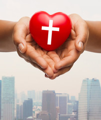 close up of hands holding heart with cross symbol