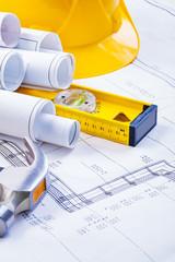 stack of rolls blueprints level hammer helmet