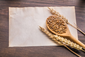 wooden spoon with coens of wheat and ears on old paper vintage w