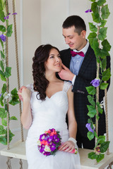 Groom hugs bride sitting on a swing with the vine