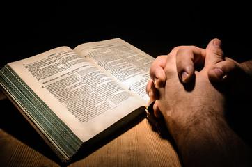 Bibel mit Händen beim Beten