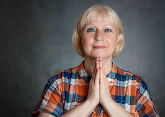 Middle aged woman praying on grey background.