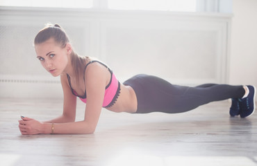 Slim fitnes young girl with ponytail doing planking exercise