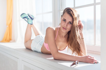 Attractive young lady  lie still near the window full of