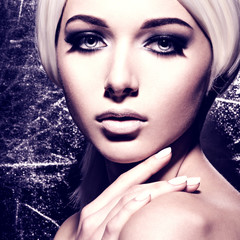 Woman's face with  fashion black makeup of eye. silver backgroun