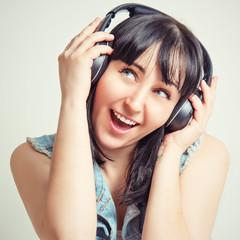 Красивая девушка в наушниках слушает приятную музыку.