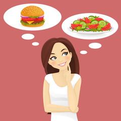 Beautiful woman choosing between salad and hamburger