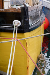 Bow of trawler boat painted bright yellow