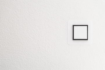 Light switch on white wall, detail shot with copy space