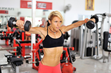 Athletic fit woman training shoulders at the gym