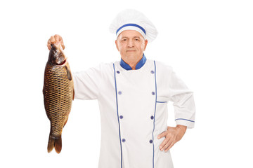 Mature male chef holding an uncooked fish