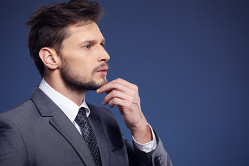 Handsome young business man standing on blue background