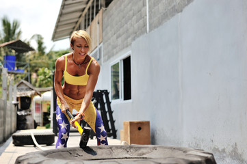 Athletic woman hit a tire by the hammer. Training on the street,