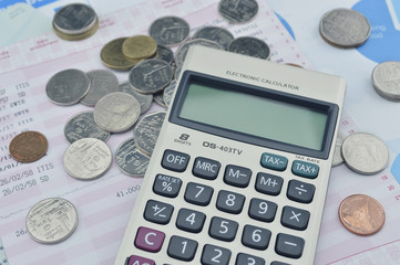 Calculator and coin on saving book