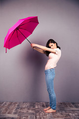 Woman holding umbrella over gray wall