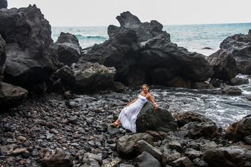 Frau im weißen Kleid an Felsenstrand