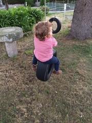 niño columpiandose sobre una rueda