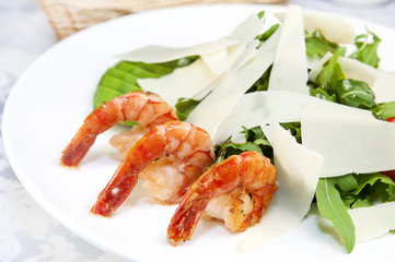 arugula dish with shrimp in a restaurant on the table