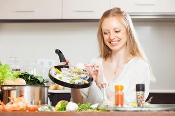 woman putting pieces lemon to fish  in frying pan
