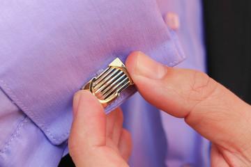 Male hand buttons cufflinks in purple shirt