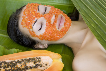 Beautiful woman having fresh papaya facial mask apply. fresh pap