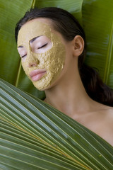 Beauty spa: Beautiful caucasian young woman with clay herbal fac