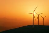 wind turbines silhouette on mountain at sunset