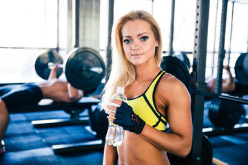 Beautiful woman holding bottle of water in gym