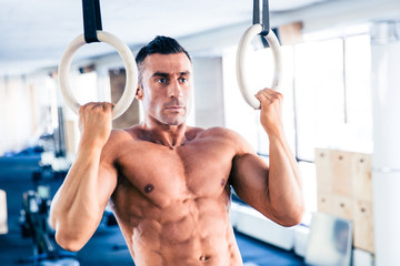 Muscular man workout on fitness ring