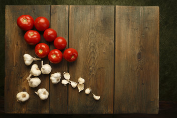 Garlic and tomatoes at a picnic table background