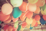 Colorful balloons floating on the ceiling of a party in vintage poster