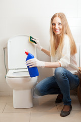 long-haired housewife cleaning toilet bowl