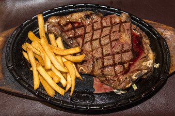 Premium American prime rib steak with french fries on a metal pl