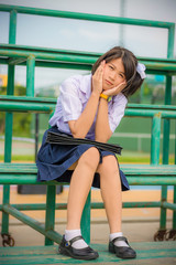Shy Thai schoolgirl sitting on a stand in childhood theme