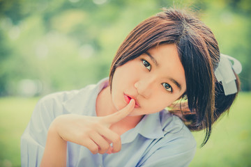 Cute Thai schoolgirl doing hush gesture in green bokeh bachgroun