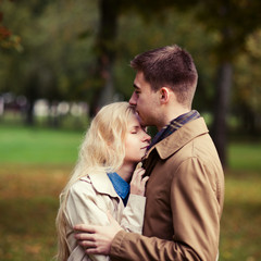 beautiful young couple kissing in the park in spring